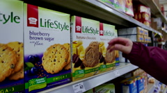 Woman selecting Lifestyle banana chocolate cookie in grocery store Stock Footage