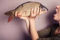 Silly young woman posing with a carp - stock photo