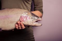Young woman holding a rainbow trout Stock Photos
