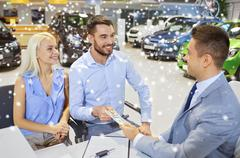 Happy couple with money buying car from dealer Kuvituskuvat