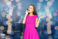 Stock Photo of happy young woman with party horn over night city