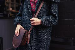 Woman in winter coat with shoulder bag - stock photo