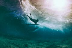 Duckdive surfer and sun reflection under water - stock photo