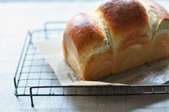 Freshly baked bread on metal grate - stock photo