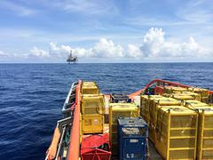 Oil rig support vessel transporting cargo to oil rig seen on horizon Stock Photos