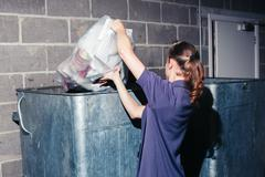 Woman putting rubbish in bin - stock photo