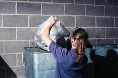 Woman putting rubbish in bin Stock Photos