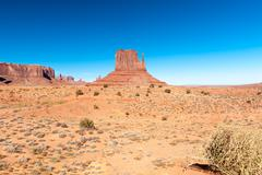 USA, Utah, Monument Valley, Monument Valley, The Mittens in barren scrubland - stock photo