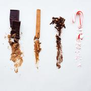 Chocolate, cinnamon, cloves, and candy cane, whole at top, crushed below Stock Photos