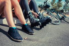 Two women sitting by roadside wearing rollerblades Stock Photos