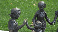 People passing by the bronze children statues in Alba Iulia fortress Stock Footage