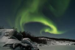 Sweden, Kiruna, Aurora Borealis above Frozen Lake of Tornetrask - stock photo