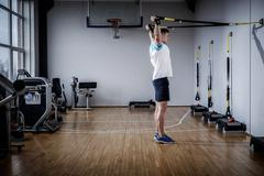 Stock Photo of Attractive man during workout with suspension straps In The Gym's Studio