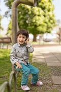 Bulgaria, Sofia, Boy (4-5) sitting on park railing talking on mobile phone - stock photo