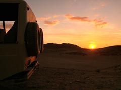 Namibia, Hoanib, 4x4 in desert at sunset - stock photo