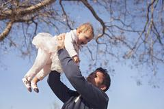 Father holding aloft smiling daughter (6-11 months) Stock Photos