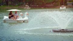 Tourists pedaling around an urban lake at Lumphini Park Stock Footage