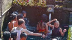 Families lined up to bathe in sacred springs of Tirta Empul temple in Bali Stock Footage
