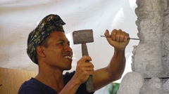 Local, Balinese sculptor, chipping at and shaping a block of stone Stock Footage