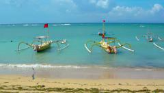 Many traditional, outrigger passenger boats, tied on a popular tourist beach Stock Footage