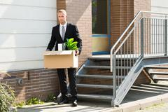 Disappointed Businessman Standing With Cardboard Box Outside Office Stock Photos