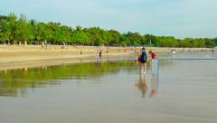 Running man, serfers and rested people on wide Kuta beach Stock Footage