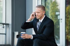 Businessman Looking At Cellphone Holding Disposal Cup Stock Photos