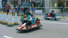 Young children racing on toy cars at a tourist attraction in Hong Kong, China Stock Footage