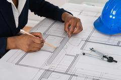 Close-up Of A Businesswoman Drawing Blueprint At Office Desk Stock Photos