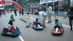 Children racing rented toy cars around a temporary track at festival Stock Footage