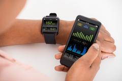 Close-up Of Hand With Mobile And Smartwatch Showing Heartbeat Rate Stock Photos
