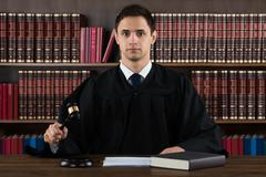 Portrait of confident judge hitting mallet at desk against bookshelf in court - stock photo