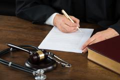 Midsection of judge writing on legal documents with mallet and stethoscope at - stock photo