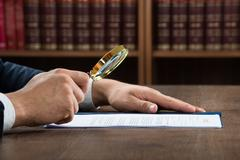 Cropped image of lawyer examining documents with magnifying glass in courtroo - stock photo
