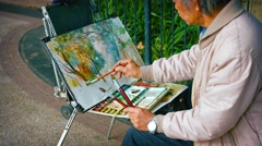 Stock Video Footage of Talented street artist paints with watercolor on his easel in Hong Kong, Chin