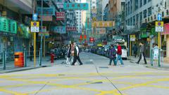 Pedestrians and parked cars on a busy, commercial street in Hong Kong, China - stock footage