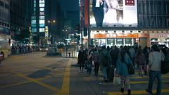 Urban intersection with pedestrian and vehicle traffic at night in Hong Kong Stock Footage