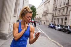 Runner checking her pulse in the street Stock Photos