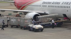 Baggage handler taking luggage from the plane to the cargo truck Stock Footage