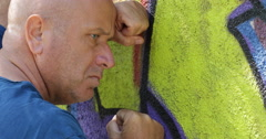 Determined Sad Men Unhappy Suffering Worried Graffiti Wall Background Close Up   Stock Footage