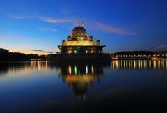 Malaysia, Putrajaya, Mosque reflecting in lake at dusk Stock Photos