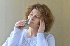 Sick with  rhinitis woman dripping nose medicine Stock Photos