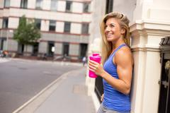 A woman out exercising having a break to rehydrate Stock Photos