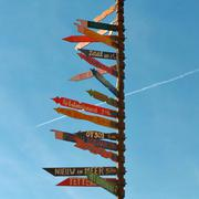Multi colored directional signs against blue sky Stock Photos