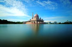 Malaysia, Putrajaya, Putra Mosque, Mosque by lake and blue sky Stock Photos