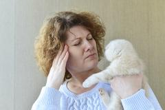 woman with allergy is holding  kitten - stock photo