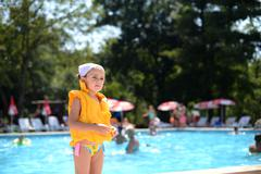 Girl standing by the pool wearing a life jacket, Thassos, Greece Stock Photos