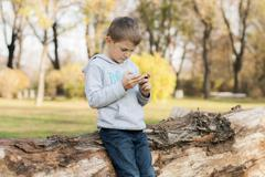 Boy leaning against tree trunk playing on mobile device in the park Kuvituskuvat