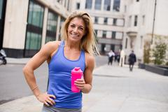 young fitness woman holding a flask of water - stock photo