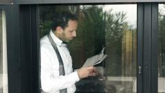 Young businessman reading newspaper and drinking tea by the window at home HD Stock Footage